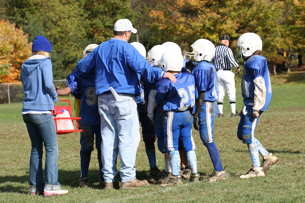 a youth football coach with his team